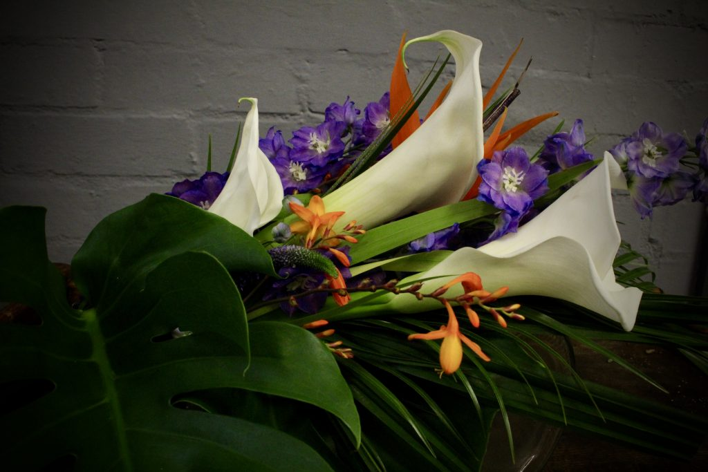 Bridal flowers. Calla, Strelitzia, Delphinium, Crocosmia, Veronica all surrounded in lush, thing green tropical leaves.